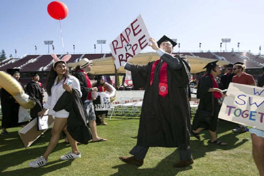 Paul Harrison, center, carries a counter-protest sign at the Stanford University graduation exercises, Sunday, June 12, 2016, at Stanford Stadium in Stanford, Calif. Women's advocacy organizations are urging a California agency to take action against the judge who sentenced a former Stanford University swimmer to six months in jail for sexually assaulting an unconscious woman. Harrison argued that the assault was not indicative of a