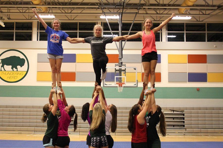The CHS Varsity cheerleading squad performs a stunt at their practice.