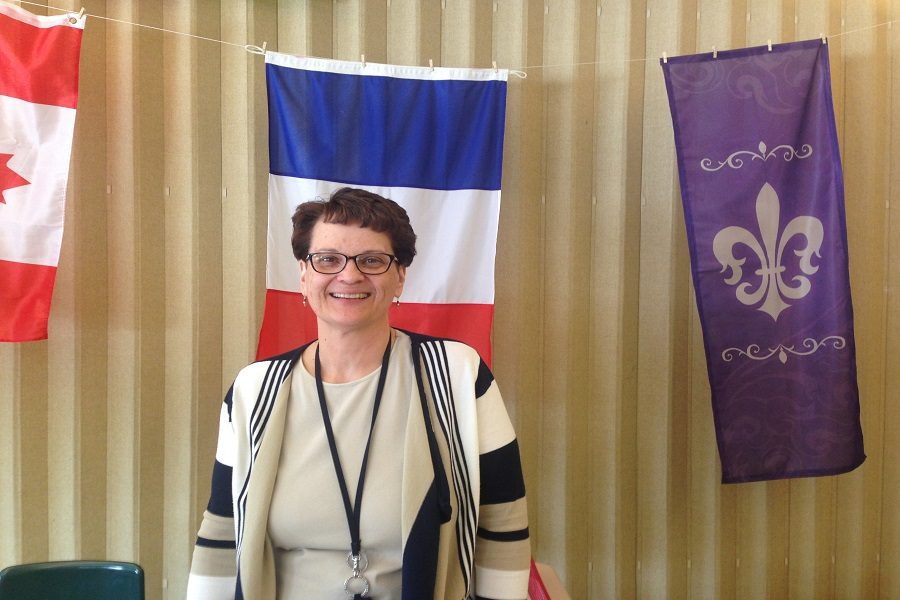 Madame Lathrop stands in front of her French Flag that is in her room.