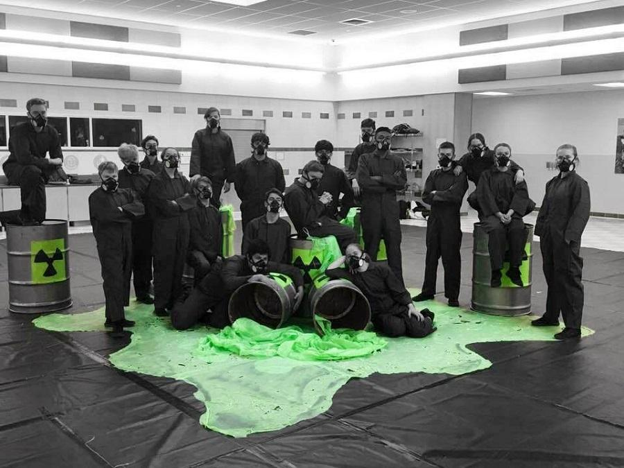 Members of indoor percussion pose with their toxic waste props in the Wilson Middle School cafeteria, where they practice.