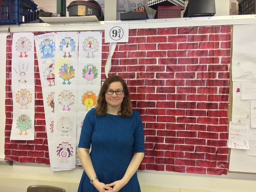 English teacher Sarah Clayville stands in front of one of her Harry Potter themed walls.
