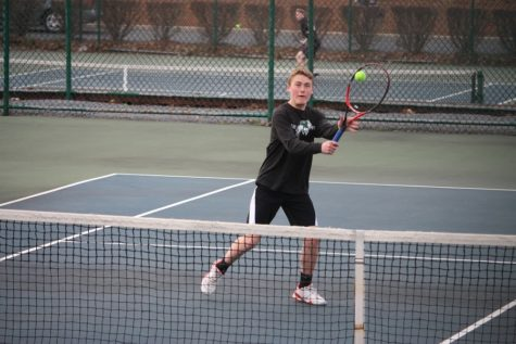 Sean Bergsten takes a volley at the net in his doubles match.