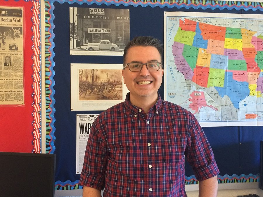 Michael Gavazzi stands in front of maps and documents in his classroom.