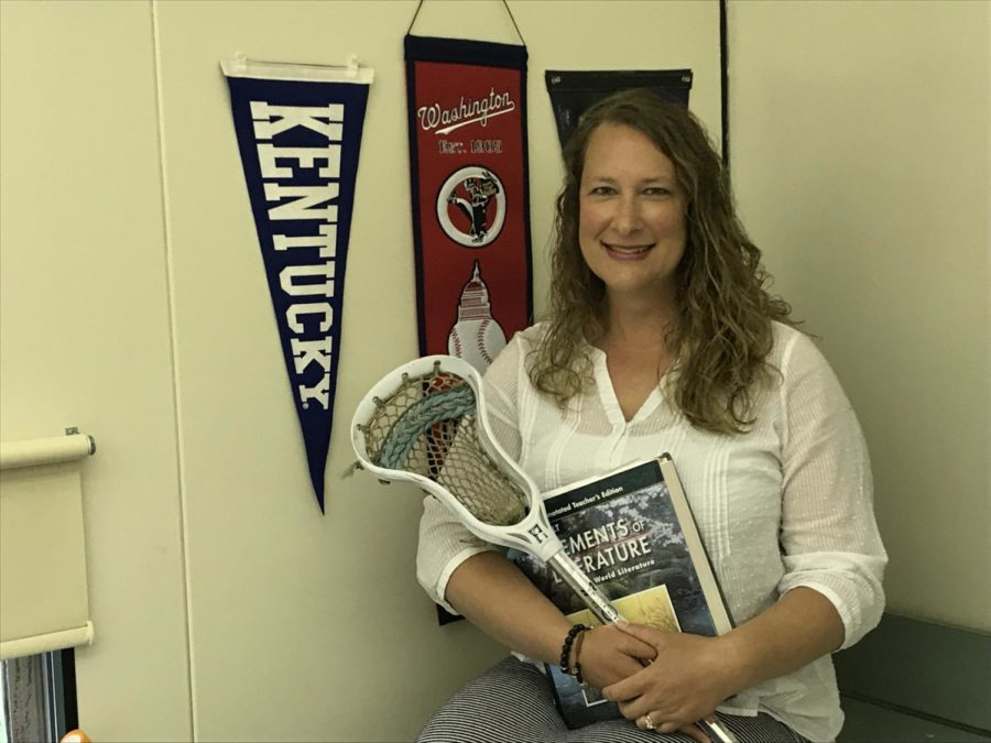 Michelle Disbrow poses with her college pennants, lacrosse stick, and English textbook in her classroom.