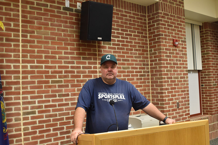 Coach Sullenberger stands at the podium ready to begin the pre-season meeting.  Sullenberger is the newly appointed coach for the upcoming 2019 spring season.