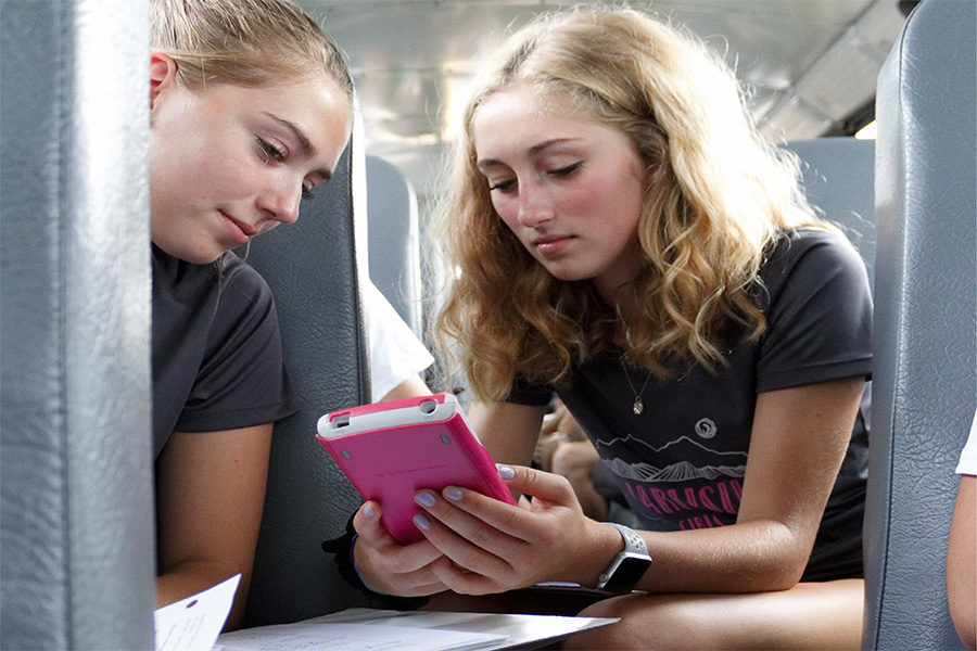 Alyssa Dyson and Mia Fry doing their homework on the bus that is taking them to an away meet. Students have to use every spare minute of their time in order to complete school work when going to their sporting events.