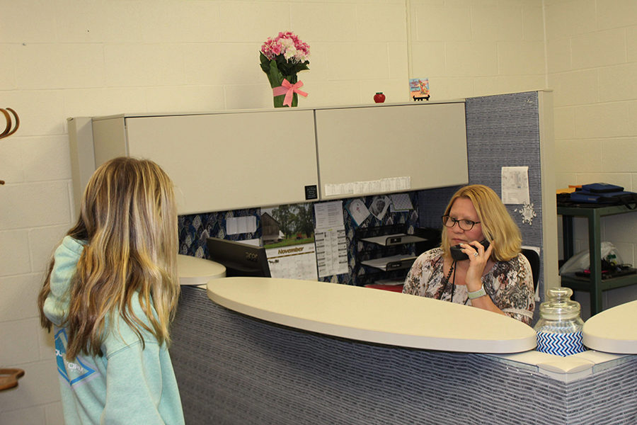 A student talks to Mrs. Sue Yingling, the Secretary to the Director of IT operations