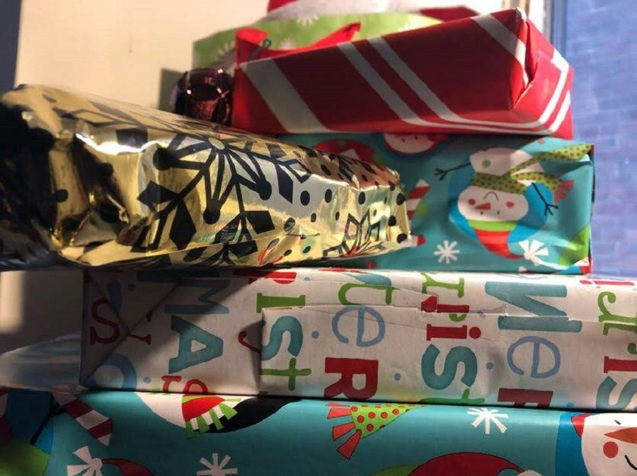 Holiday gifts are stacked up, ready to be given. Gifts like these were distributed to families in need by the Adopt-a-Family program.