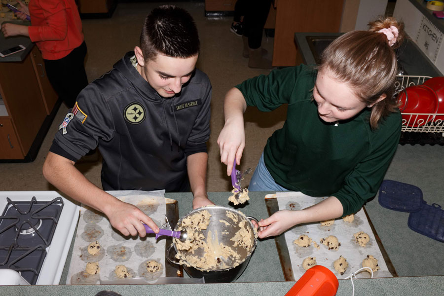 Junior MJ Brown and sophomore Mabel Sheesley scoop chocolate chip cookie dough onto baking sheets.  Student Council made 130 dozen cookies for this year's Project Share collection.