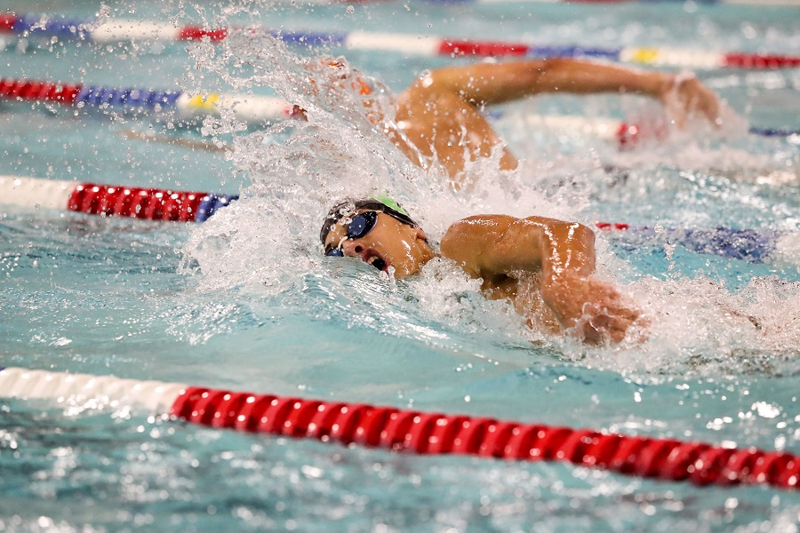 Isaiah Bell swims freestyle during a swim meet.  Bell is a senior captain on the varsity team this season.