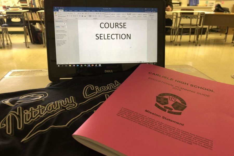 A course selection booklet sits with a Penn State pennant. Penn State classes will no longer be offered at Carlisle High School after this school year.
