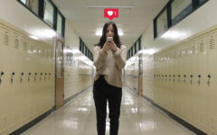 A student stands in a hallway staring at her phone, looking over Instagram.