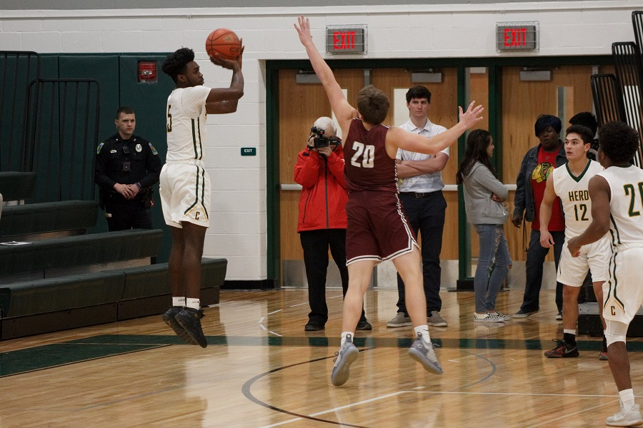 Senior Dayne Grays shoots a three-pointer during the first quarter of the game vs State College.  Grays scored 7 points in the 54-39 upset win on senior night.
