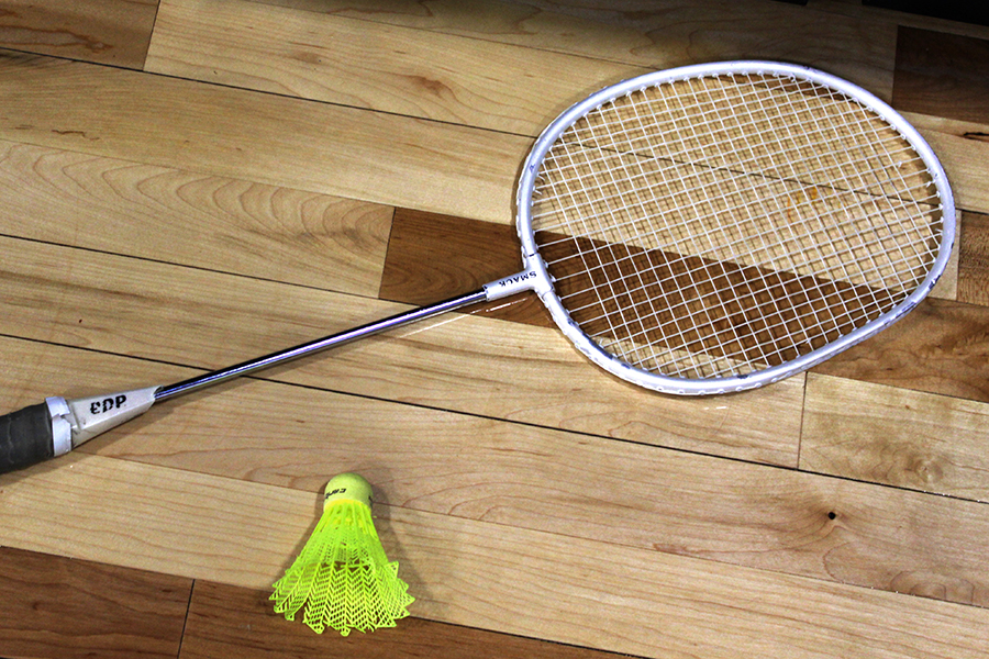 A badminton racket and birdie layed out on the floor of the gym.  Badminton is one of the favorite units of the year.