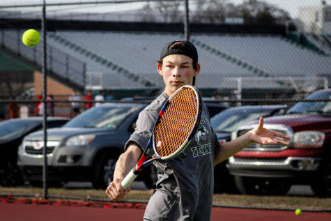 Varsity player Matthew Presite prepares to volley a tennis ball over the net. This is Presite