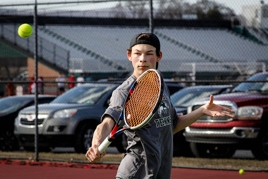 Varsity player Matthew Presite prepares to volley a tennis ball over the net. This is Presite's final year on the tennis team.