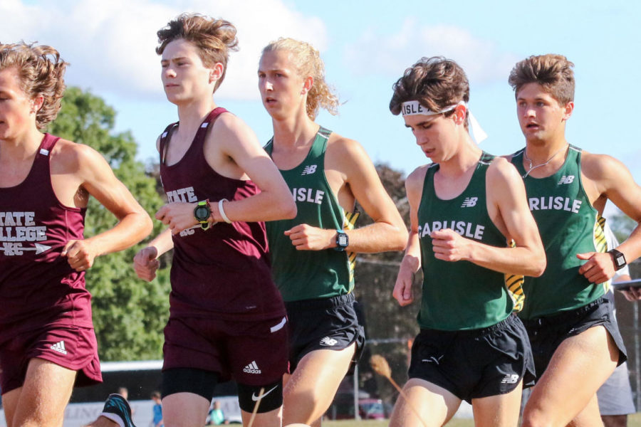 Senior Casey Padgett runs in amongst State College and Carlisle runner during a meet.  Padgett has been a key leader for the team, following in the footsteps of his siblings who also ran for Carlisle XC.