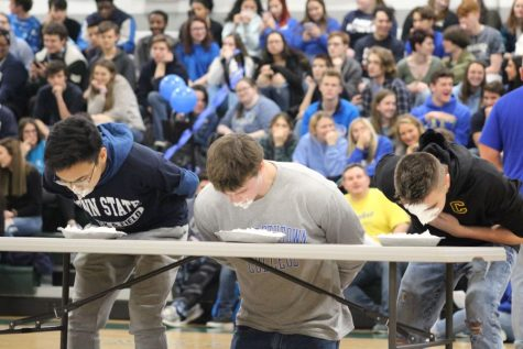 "Winter Ball court members Michael ""MJ"" Julias, Eric Hoover, and Marty ""MJ"" Brown, all seniors, participate in a pie eating contest.  This was one of the highlights of the Winter Ball pep rally."