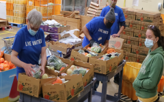 WORKING TOGETHER: Volunteers at the Project SHARE's warehouse package fruits and vegetables for the families they serve. Since the pandemic started, the food bank has seen an 18% increase in households served.