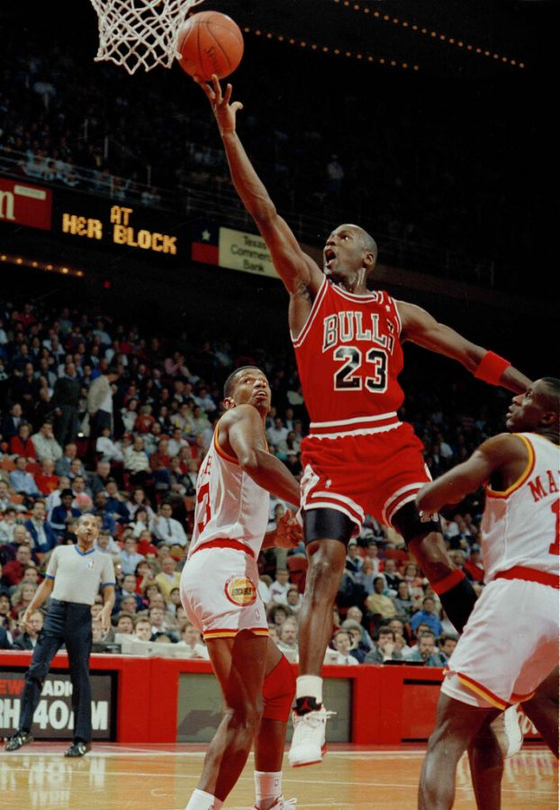 FILE - In this Jan. 3, 1991, file photo, Michael Jordan (23) of the Chicago Bulls drives the lane for a finger roll lay-up over Otis Thorpe, left, and Vernon Maxwell, right, of the Houston Rockets in the first half in Houston, Texas. Picking the car number for Michael Jordan's new NASCAR team was a slam dunk: Bubba Wallace will drive the No. 23 car when the team makes its debut next season. (AP Photo/David Scarbrough, File)