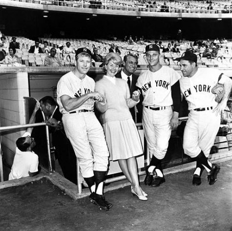 "Actress Doris Day and actor Cary Grant, standing in the dugout, pose with New York Yankees players, from left, Mickey Mantle, Roger Maris and Yogi Berra before the Yankees-Dodgers game in Los Angeles, Ca., July 12, 1962.  The players appeared in the movie ""A Touch of Mink"" with Day and Grant.  (AP Photo/Ed Widdis)"