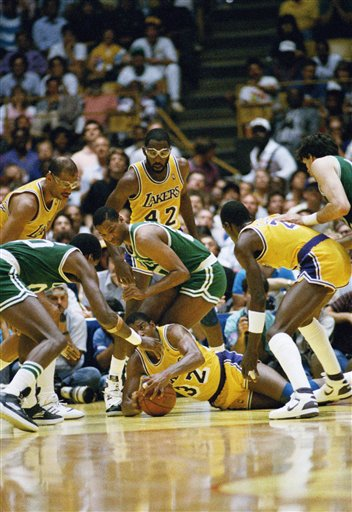 Earvin Magic Johnson of the Los Angeles Lakers scrambles for the ball on the floor of The Forum during the NBA finals, Tuesday, June 2, 1987, Inglewood, Calif. Johnson is surrounded by  unidentified Boston Celtics players. Kareem Abdul-Jabbar is at left. (AP Photo/Mark Avery)