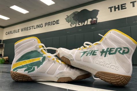 Carlisle High School inspired custom wrestling shoes sit in the middle of the wrestling room. After the Thundering Herd