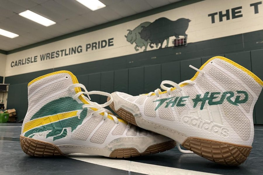 Carlisle+High+School+inspired+custom+wrestling+shoes+sit+in+the+middle+of+the+wrestling+room.+After+the+Thundering+Herd%27s+long+practice+spent+preparing+for+the+2021+season.+The+Herd+look+to+improve+upon+their+8-7+season+a+year+ago.